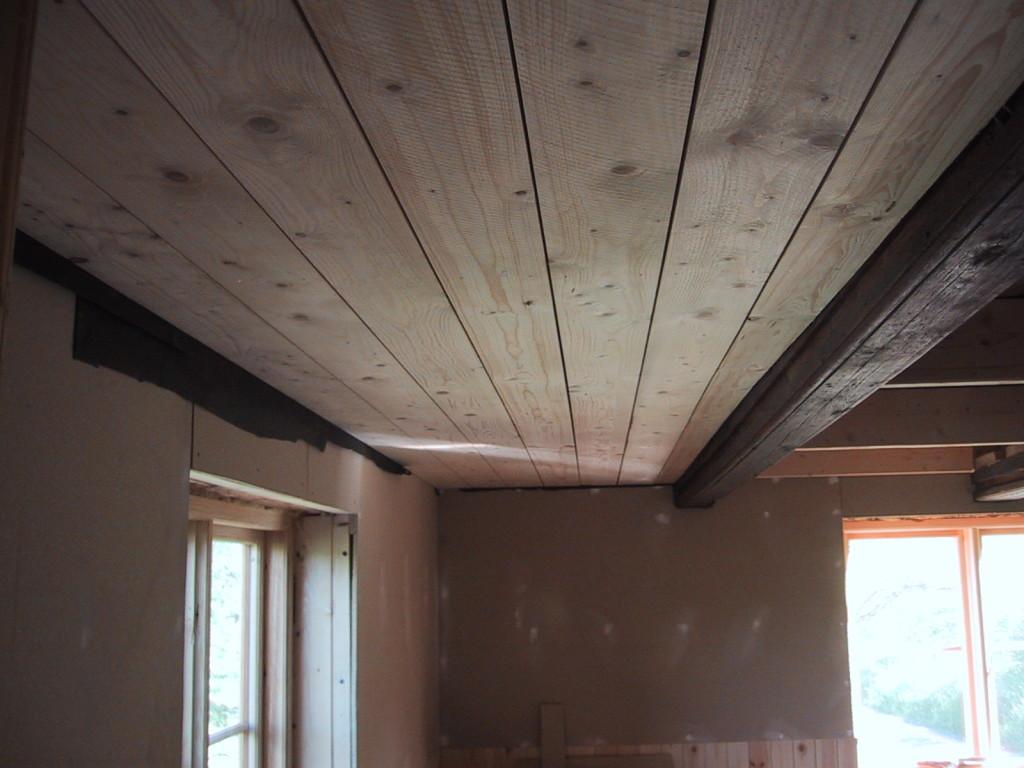 Taket får vitbetsade brädor och stockarna målar jag med hemblandad linoljefärg efter att bänt bort 3 miljoner nubb efter papptaket!