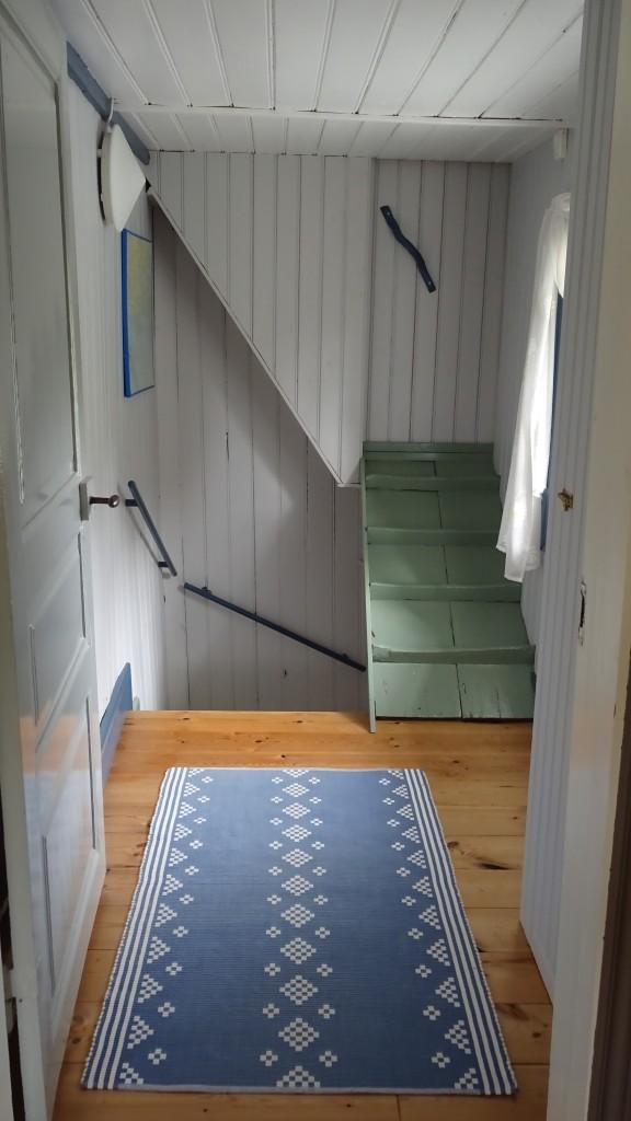 Hallen med nyskurat golv och hönstrappan upp till loftet